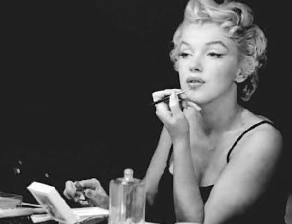 Marilyn Monroe putting on her makeup with makeup and perfume in front of her